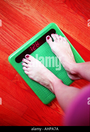 Woman standing on scale feet on scale 'Diet concept' - Stock Photo