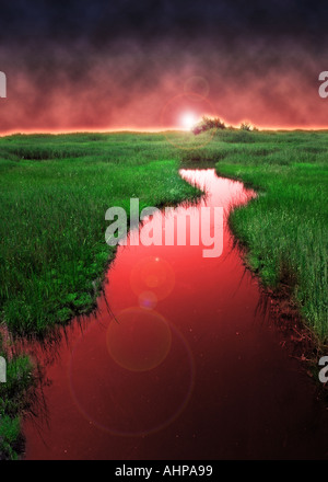 surreal red river running into green landscape with a curve bend in the flowing water - Stock Photo