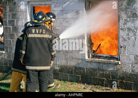 Fireman hosing down a burning building - Stock Photo