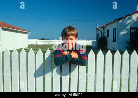 Boy standing at white picket fence Pacific Grove California - Stock Photo
