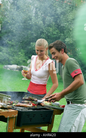 Friends cooking on barbecue - Stock Photo