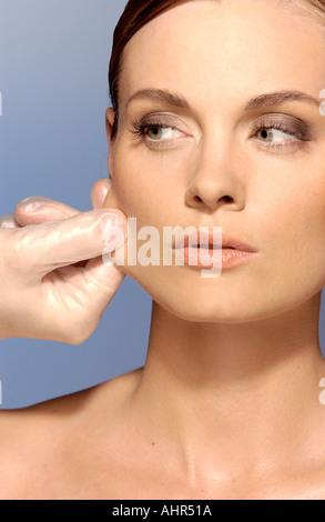 Surgeon pulling woman's skin - Stock Photo
