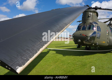 A Boeing CH 47 Chinook with the rotor blades all tied down and one of them in close up in the foreground - Stock Photo