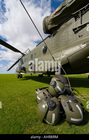 A Boeing CH 47 Chinook with the rotor blades all tied down and the crew s helmets in the foreground - Stock Photo