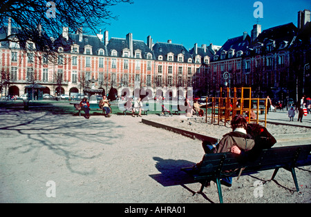 Paris France Parks 'Couple on Bench' in 'Place des Vosges' Le Marais Neighborhood  Man Woman Outside Youth Garden - Stock Photo