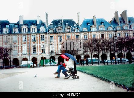 Paris France Parks Couple Sitting on 'Park Bench' With Umbrellas in the Rain 'Place des Vosges' 'Historic Architecture' - Stock Photo