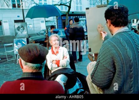 Paris France Montmartre 'Place du Tertre' SIDEWALK artist Painting Portrait of Woman Tourist - Stock Photo