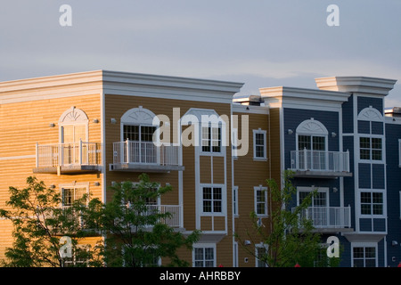 Condominiums in yellow and blue against the light of the setting sun - Stock Photo