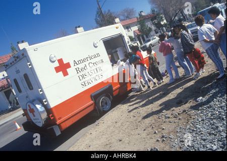 A worker in an American Red Cross Disaster Service vehicle handing out supplies to people after the 1994 earthquake - Stock Photo