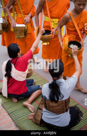 Local women give Alms to monks in Luang Prabang Laos - Stock Photo