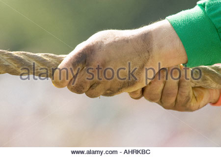 hands holding a rope while playing tug of war - Stock Photo