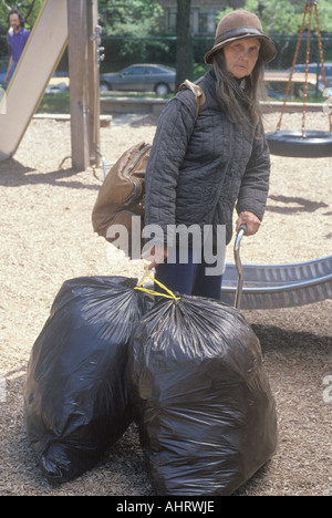 Elderly homeless woman holding possessions in garbage bags Chicago Illinois - Stock Photo
