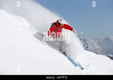 Austria, Saalbach, male skier turning in snow on slope - Stock Photo