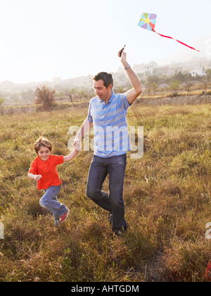 Father and son (4-6) running in field with kite, smiling - Stock Photo