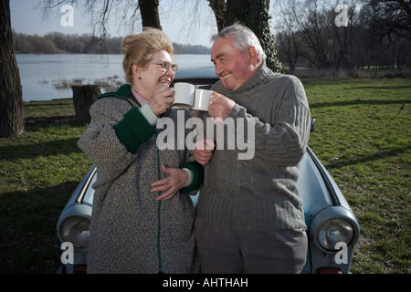 Senior couple standing by car toasting each other with cups, smiling - Stock Photo