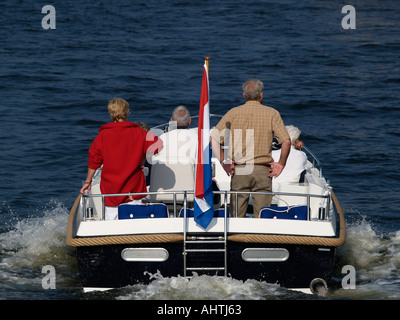 Four older people two elderly couples heading towards adventure in their motoryacht Amsterdam the Netherlands - Stock Photo