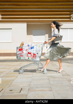 Woman pushing supermarket trolley against wind, Alicante, Spain, - Stock Photo