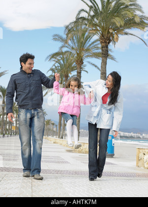 Mother and father walking along palm lined pavement by the sea swinging young daughter (6-8). Alicante, Spain. - Stock Photo