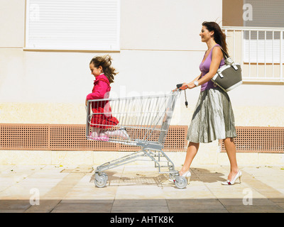 Mother pushing daughter (5-7) in supermarket trolley, Alicante, Spain, - Stock Photo
