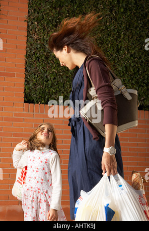 Low angle view of mother and daughter (5-7) carrying shopping bags, Alicante, Spain, - Stock Photo