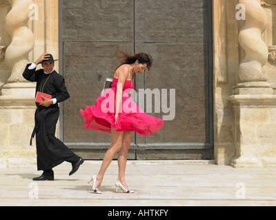 Priest passing woman whose skirt is blowing up in the wind, Alicante, Spain, - Stock Photo