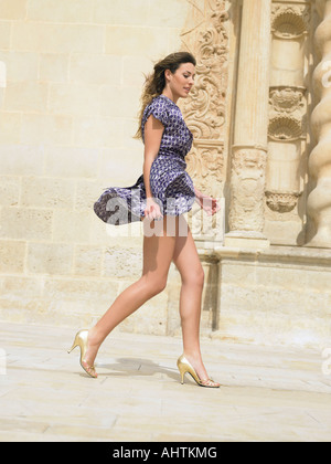 Young woman walking with her skirt blowing in the wind, Alicante, Spain, - Stock Photo