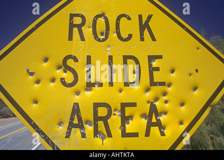 Bullet holes in a Rock Slide Area sign Southern California - Stock Photo