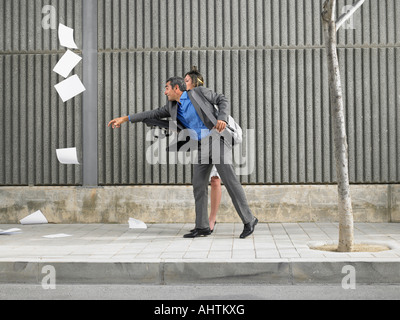Older man and young woman chasing papers blown by the wind down the pavement, Alicante, Spain, - Stock Photo