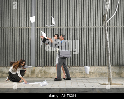 Older man and young woman chasing papers blown by the wind down the sidewalk, being helped by another woman, Alicante, - Stock Photo
