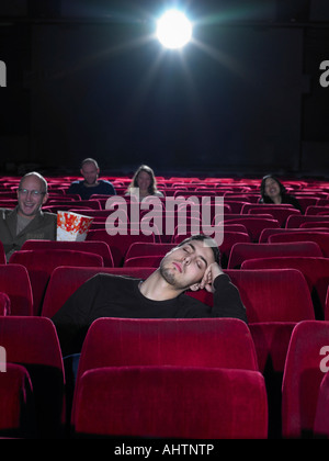 Young man asleep in cinema - Stock Photo