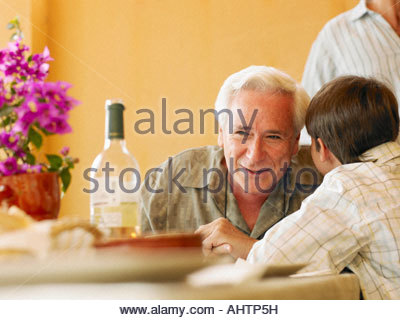 Boy (8-10) whispering in grandfather's ear at dining table - Stock Photo