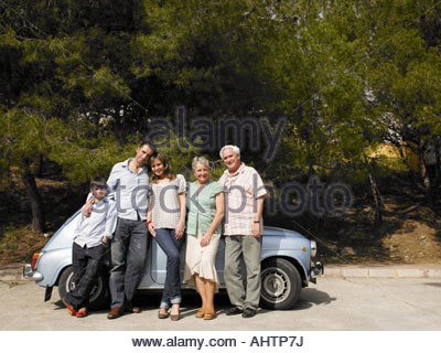 Multi-generational family standing beside car, smiling, portrait - Stock Photo