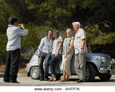 Multi-generational family standing beside car, boy (8-10) taking photo - Stock Photo