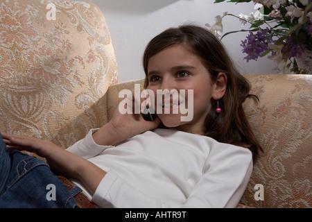 Girl (9-11) using mobile phone lying on sofa, smiling - Stock Photo
