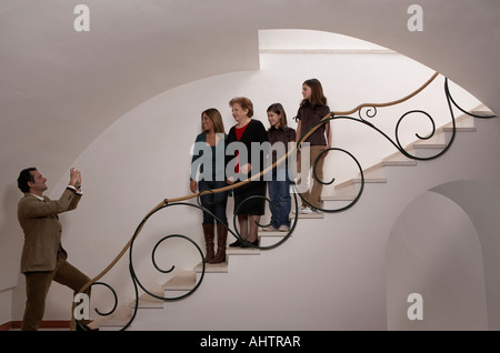 Three generation family on staircase posing for photograph - Stock Photo