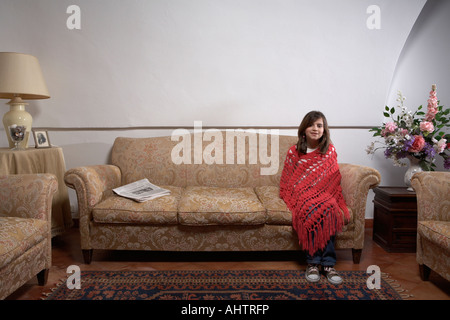 Girl (9-11) sitting on a sofa in a living room, portrait - Stock Photo