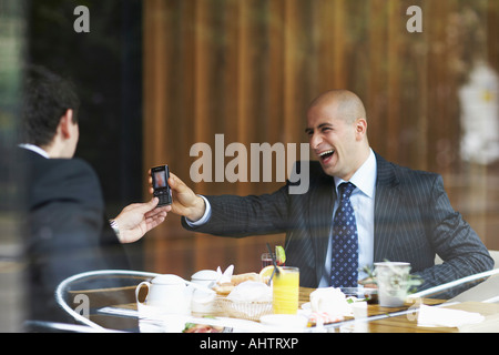 Two businessmen in a restaurant looking at a cell phone - Stock Photo