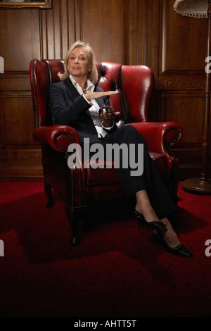Businesswoman in a comfy leather chair with a candle - Stock Photo