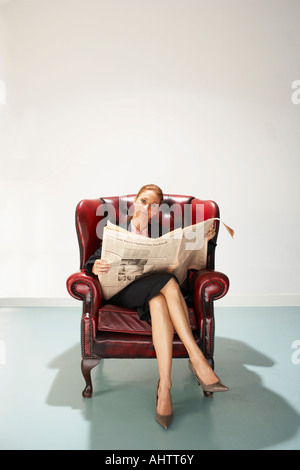 Businesswoman in a comfy leather chair with newspaper - Stock Photo