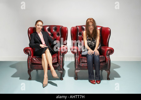 Businesswoman and disheveled woman in comfy leather chairs - Stock Photo