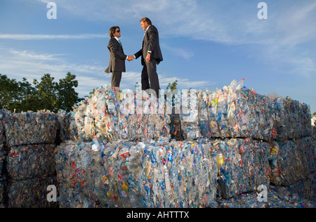 Businessmen shaking hands at a recycling plant. - Stock Photo