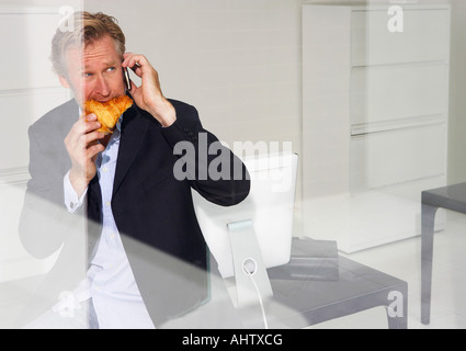 Man in office eating croissant on telephone with reflections. - Stock Photo