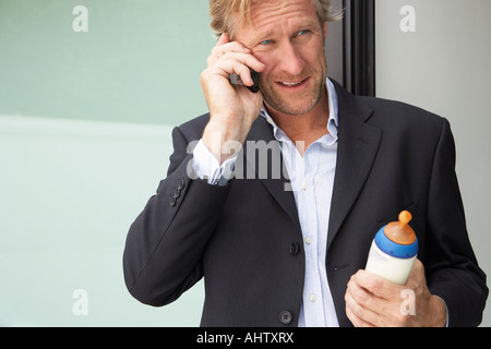 Businessman using mobile phone whilst holding baby's bottle. - Stock Photo