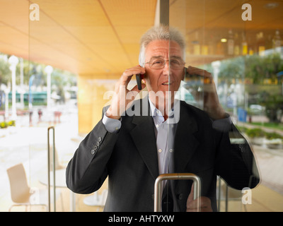 Man on his cell phone half out a doorway. - Stock Photo