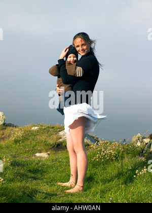 Young woman holding baby with the wind blowing her skirt. - Stock Photo
