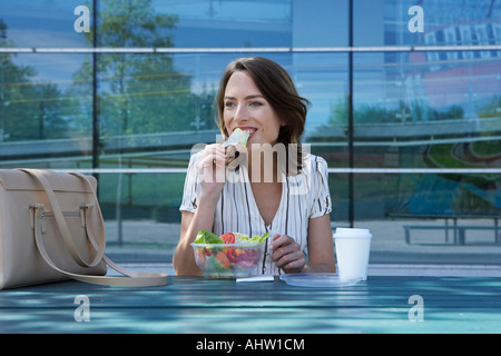 Businesswoman on table in front of office outside biting off salad to go. - Stock Photo