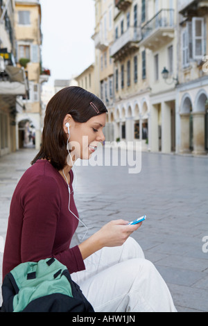 Young girl sitting on steps in street earphones in ears MP3 in hand smiling old city in background. - Stock Photo
