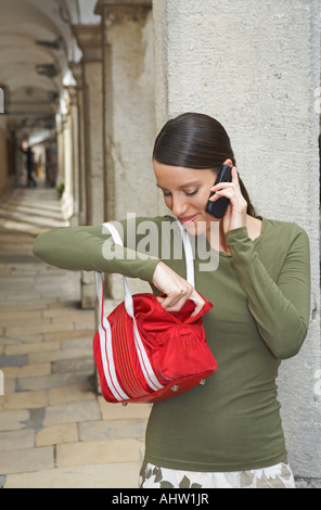 Young woman leaned at wall of ambulatories on the mobile fishing something out of her handbag smiling. - Stock Photo