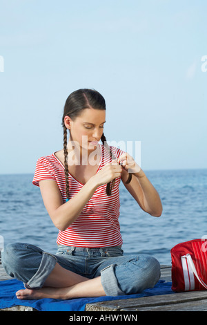 Young girl sitting on jetty plaiting herself pigtails. - Stock Photo