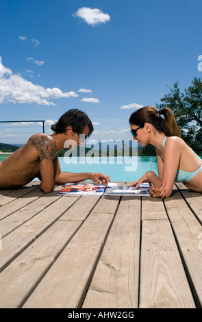 Couple sunbathing by a swimming pool with magazines
